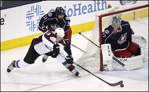 Columbus Blue Jackets' Fedor Tyutin (51) pushes Colorado Avalanche's Jamie McGinn (11) from behind as he tries to score on goalie Sergei Bobrovsky during the third period.