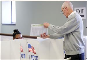 Poll worker John Flahie, right, helps first time voter Tyesha Fleming, left, 18, from Toledo, understand the paper voting system during the first day of voting at the Lucas County Early Vote Center.