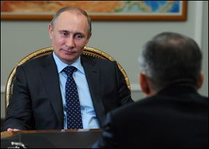 Russian President Vladimir Putin, left, speaks to Tatarstan regional leader Rustam Minnikhanov, back to camera, during a meeting at the Novo-Ogaryovo residence outside Moscow, Russia today.