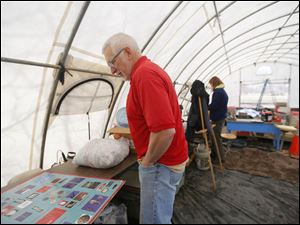 David Bush, chair of the Friends and Descendants of Johnson's Island Civil War Prison, works inside of the weather tent to prepare for Saturday's