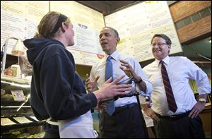 President Obama, accompanied by Rep. Gary Peters (D., Bloomfield Hills, Mich.), right, talks with employee Andrea Byl to order lunch during their visit to Zingerman's Deli in Ann Arbor. After eating his Reuben sandwich on Wednesday, the President traveled to the University of Michigan to speak about his proposal to raise the national minimum wage.