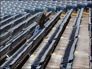 Kevin Burwell of Toledo Building Services inspects the seats to make sure they are clean.