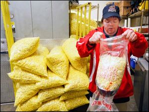 William Hartford bags popcorn in preparation for opening day.