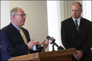 Paul Toth, President & CEO of the Toledo-Lucas County Port Authority, right, listens as Toledo Mayor D. Michael Collins, left, addresses the  future operations of the Toledo Express Airport.