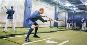 Mud Hens infielder Mike Hessman practices in an indoor batting cage.