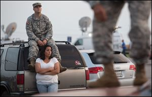 Lucy Hamlin and her husband, Spc. Timothy Hamlin, wait for permission to re-enter the Fort Hood military base, where they live, following a shooting on base on Wednesday.
