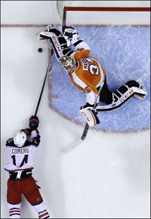 Columbus Blue Jackets' Blake Comeau, left, tries to get a shot past Philadelphia Flyers goalie Steve Mason during the first period Thursday in Philadelphia.