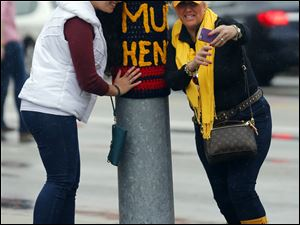 Audrey Mays, left, Dayton, and Cathy Trimble, Monclova, take a selfie near a Mud Hens yarn bomb on a pole near the stadium.