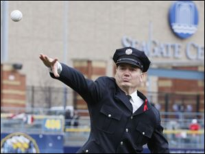 Toledo firefighter Mark Klemner throws out one of the first pitches.