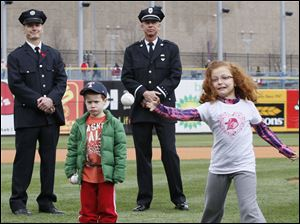 Grace Hoye, 8, niece of fallen firefighter Stephen Machcinski, throws out one of the first pitches. Next to her is brother Brandon Hoye.