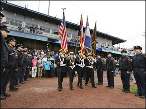 The Toledo Firefighter honor guard presents the colors during the Mud Hens season opener against Louisville on Friday at Fifth Third Field.