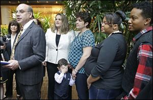 Attorney Al Gerhardstein, left, stands with several same-sex couples at a news conference Friday in Cincinnati. Mr. Gerhardstein said 'this [gay marriage ban] is a serious problem at the basic level of human dignity.'