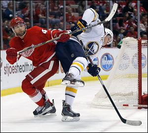 Detroit's Jakub Kindl knocks Buffalo's Luke Adam off-balance during the first period on Friday night.