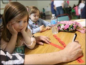 Kristin Humphries, left, filled out raffle tickets under the watchful eye of Avery, 3, left.