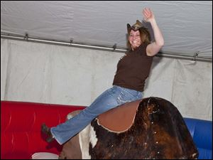 Jen Richardson rides the mechanical bull at the Boots, Bling & Barbecue event.