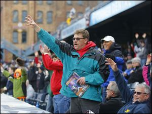 John Scobie, Blissfield, looks for a free shirt with others during opening day festivities.