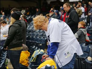 Season ticket holder Nancie Meacham, Erie Township, Mich., bows for a moment of silence honoring fallen Toledo firefighters.