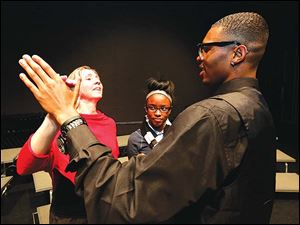 Dance teacher Jennifer Jarrett, left, helps Dayshawn Jones, right, a senior, understand the amount of hand pressure needed for the leader in the waltz. At center is Lyric Carter, a junior. Dayshawn Jones is the president of Young Men of Excellence at Woodward High School.