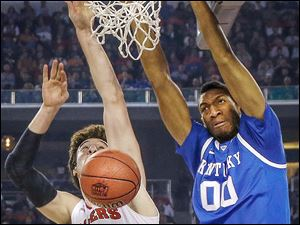 Kentucky forward Marcus Lee, right, dunks the ball over Wisconsin forward Frank Kaminsky during the first half.