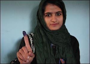 An Afghan young woman shows her inked finger after casting her vote at a polling station in Herat, Afghanistan, Saturday, April 5, 2014. Afghans flocked to polling stations nationwide on Saturday, defying a threat of violence by the Taliban to cast ballots in what promises to be the nation's first democratic transfer of power. (AP Photo/Hoshang Hashimi)