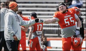 Bowling Green coach Dino Babers fist bumps lineman Alex Huettel. The offense averaged about two plays per minute in Saturday's spring game at Perry Stadium as 11 receivers caught passes.