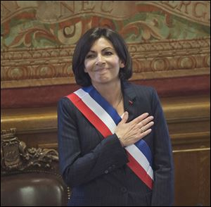 The new mayor of Paris Anne Hidalgo, wearing the mayoral sash in the color of the French Republic, acknowledges applause after her election today in Paris.