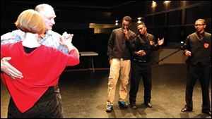 Instructors Jennifer Jarrett and Dave Morris demonstrate the waltz to Woodward High School students Daijour Whittington, left, Isaiah Jefferson, and Dayshawn Jones.