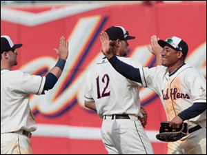 Ezequiel Carrera, right, high-fives his teammates after the Mud Hens clinched the win.