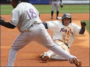 Ezequiel Carrera slides into third as Lousiville's Ruben Gotay  calls for the ball.
