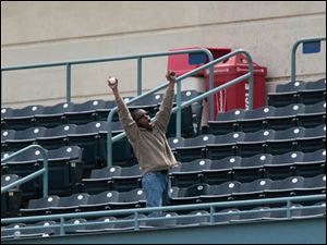 A lone fan cheers after nabbing a foul ball in the top of the second inning.