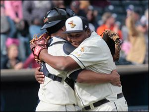 Toledo's catcher Louis Exposito, left, embraces closing pitcher Melvin Mercedes after clinching the win.