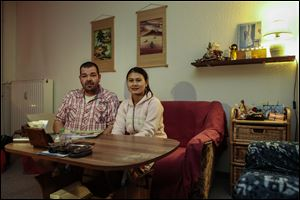 Michael Guhle and his wife Thi An Nguyen from Vietnam sit in their apartment at the Weissensee district in Berlin, Germany.