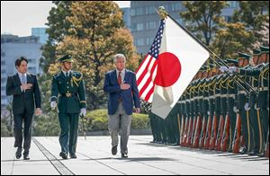 U.S. Secretary of Defense Chuck Hagel, right, reviews honor guards accompanied by Japanese Defense Minister Itsunori Onodera, left, in Tokyo on Sunday.
