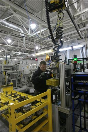 Jeff Roe of Oregon puts the valve guides into a six-speed transmission at the Toledo plant on Alexis Road. The line on which he works has been extended to allow the production of both six and eight-speed transmissions on the same line.