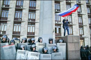 An activist waves a Russian national flag above Ukrainian police at the regional administration building in Donetsk, Ukraine, on Sunday. Protest leaders want lawmakers to discuss a vote on joining Russia.