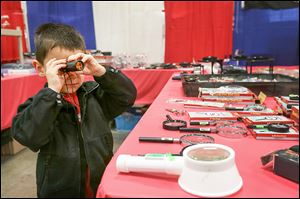 Samuel Wise, 4, of Whitehouse takes a closer look at model-crafting tools as he and his father, Brian, walk through the vendors' stalls during Sunday's expo.