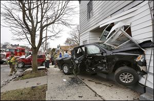 Emergency crews survey the scene after a pickup and an SUV collided, sending the truck into the side of a central-city duplex. The truck was eastbound on Hamilton Street just before 10 a.m. Monday when it collided with the Jeep Grand Cherokee, which was northbound on North Miller Street, Toledo police said. Three people were taken to local hospitals.