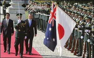 Australian Prime Minister Tony Abbott, center, reviews an honor guard during a welcome ceremony with Japanese Prime Minister Shinzo Abe, left, at Akasaka State Guest House in Tokyo  today. Abbott is on a four-day official visit.