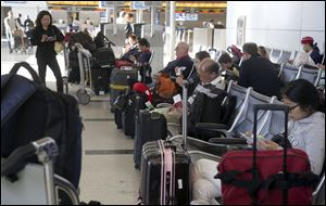 Passengers with their luggage wait for flights at Los Angeles International Airport in Los Angeles. According to a new report, the rate of lost, stolen or delayed bags rose 5 percent in 2013.