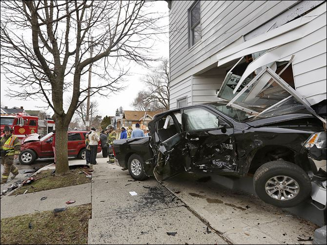 CTY crash07p Emergency crews survey the scene after a pickup and an SUV collided, sending the truck into the side of a central-city duplex. The truck was eastbound on Hamilton Street just before 10 a.m. Monday when it collided wi