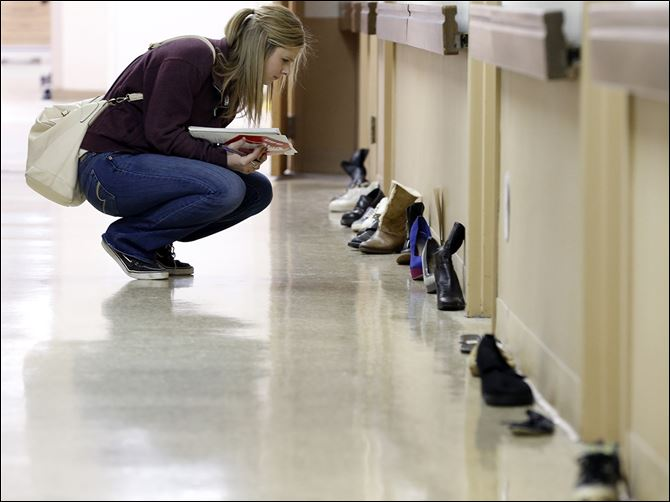 n3suicide-4 Stephanie Simon, a nursing student at Owens Community College, kneels along a path of shoes — a visual path for healing and education —at Mercy College in Toledo. The shoes belong to victims of suicide. Mercy hosted the 'Step Up. Stop Suicide' event to increase awareness in Northwest Ohio.