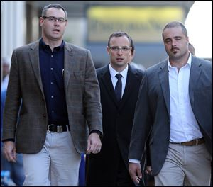 Oscar Pistorius, center, accompanied by his relatives, walks towards the high court in Pretoria, South Africa, Tuesday.
