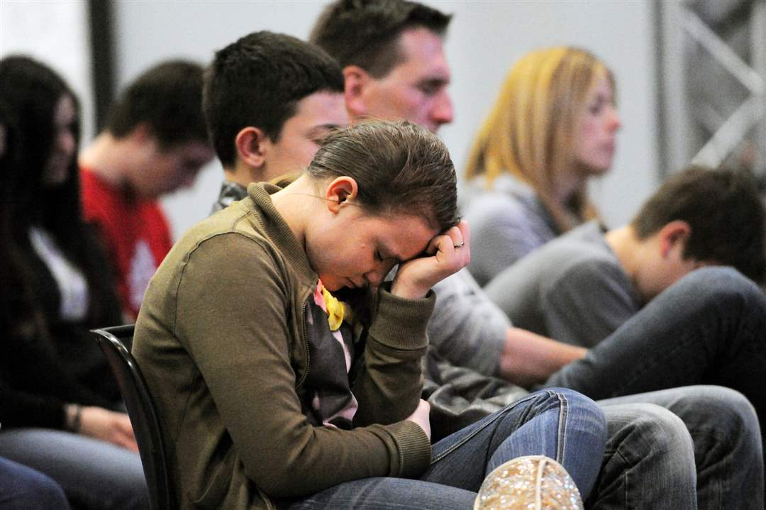 Students-and-their-families-and-friends-pray-during-service