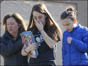 A parent escorts distraught students from the Franklin Regional Middle School where students were sent following the stabbing.
