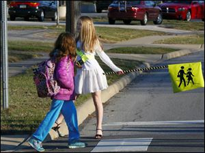 Crossing guard Lizzy Lucal, right, helps the lead student from the first walking school bus.