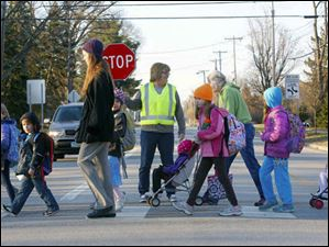 Kim Hartzell, center, holds a stop sign up to stop traffic while students in a