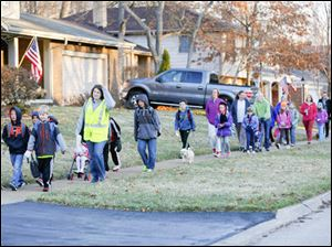 Melissa Hallenbeck, from ProMedica, wears a yellow reflective vest as she leads one of the first walking school buses down Vicksburg Dr.
