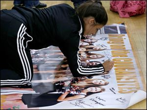 Southview dance team member and senior Stephanie Meyer signs a dance portrait poster after it was auctioned off.