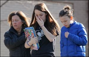 A parent escorts distraught students from Franklin Regional Senior High School, where 21 students and a security guard were injured during a Wednesday attack by a 16-year-old with two 8-inch steel knives.