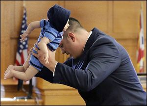 Frank Spryszak, an assistant Lucas County prosecutor, demon-strates to the court with a doll how 6-month-old Avery Bacon suffered the injuries that caused his death in December, 2012.